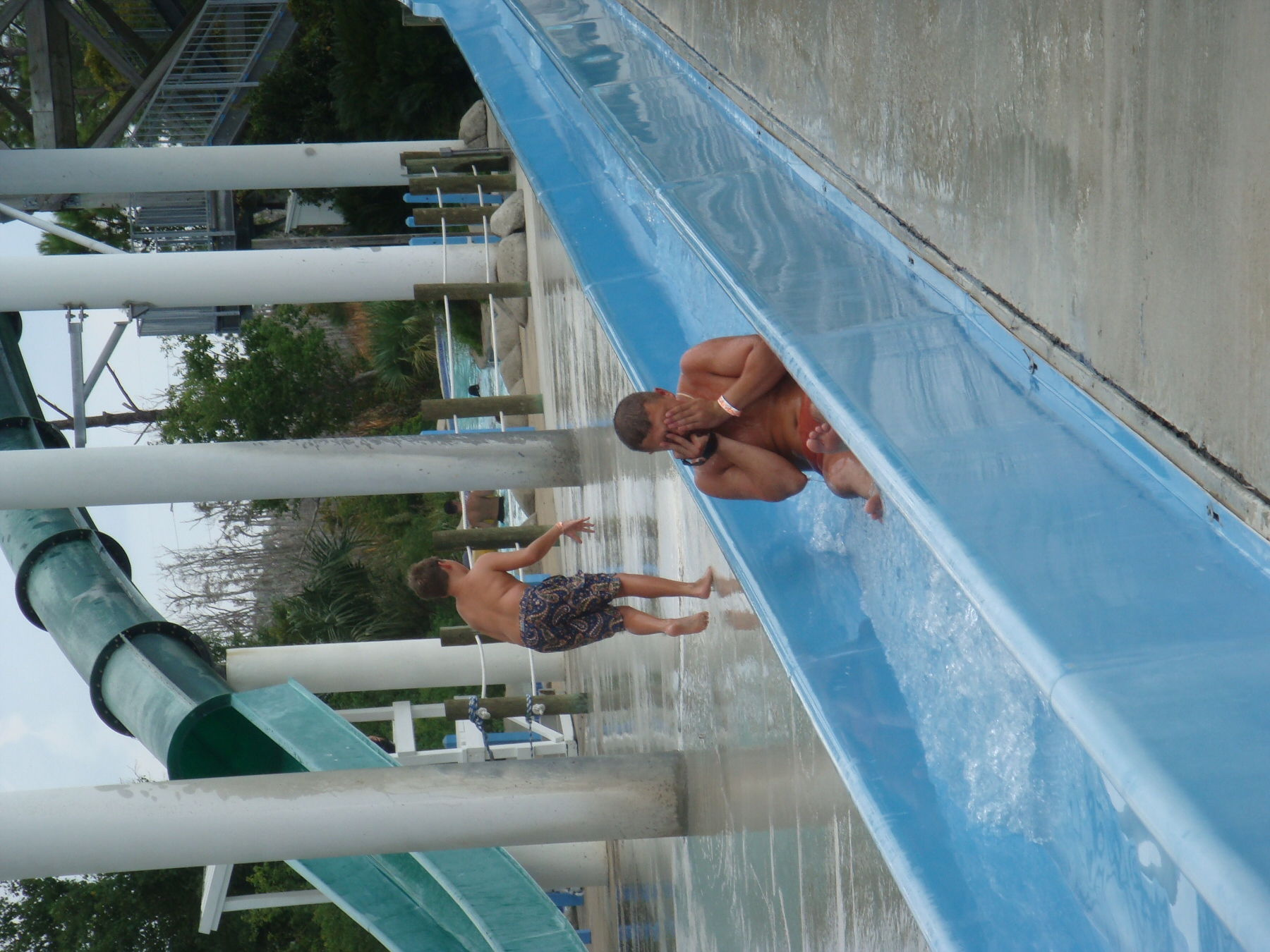 man sliding down water slide