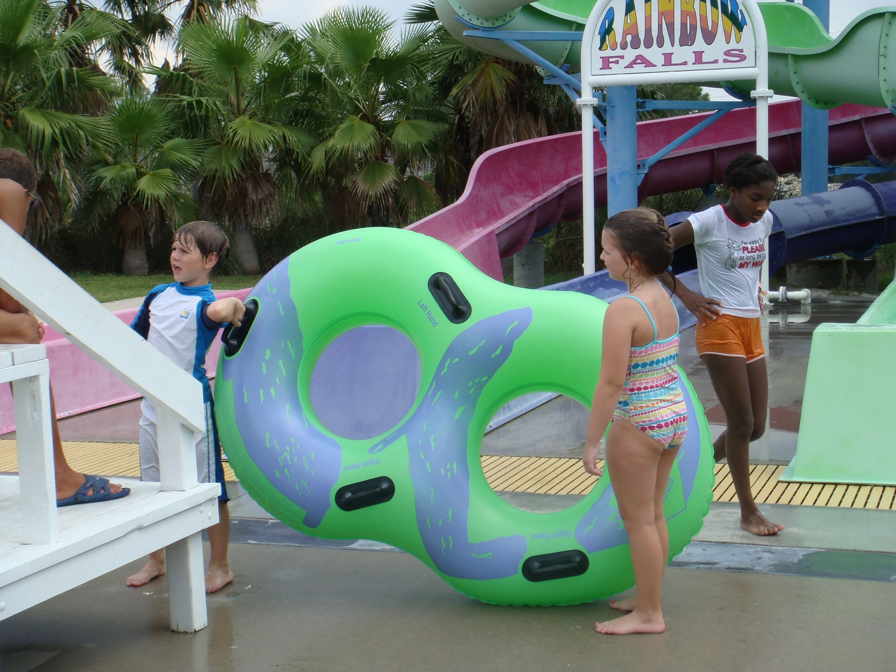 kids carrying pool float
