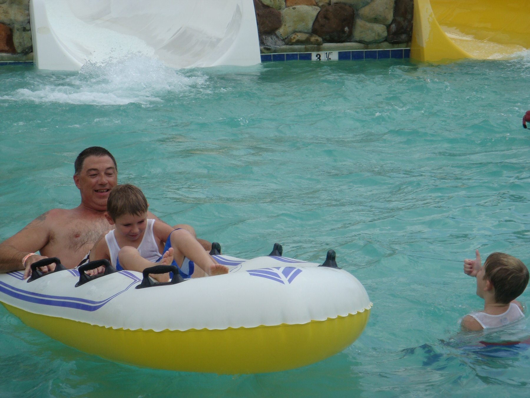 man and kid floating in pool on raft