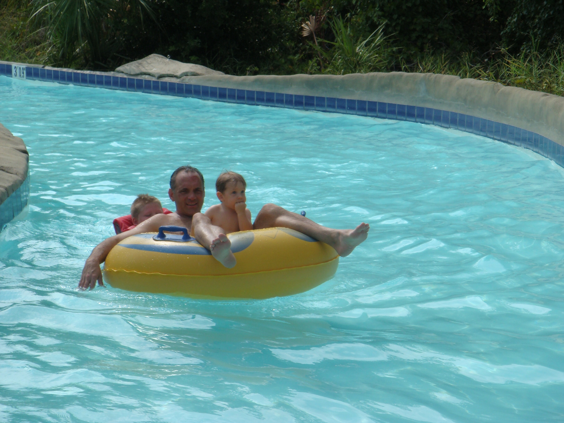 man with children floating down lazy river