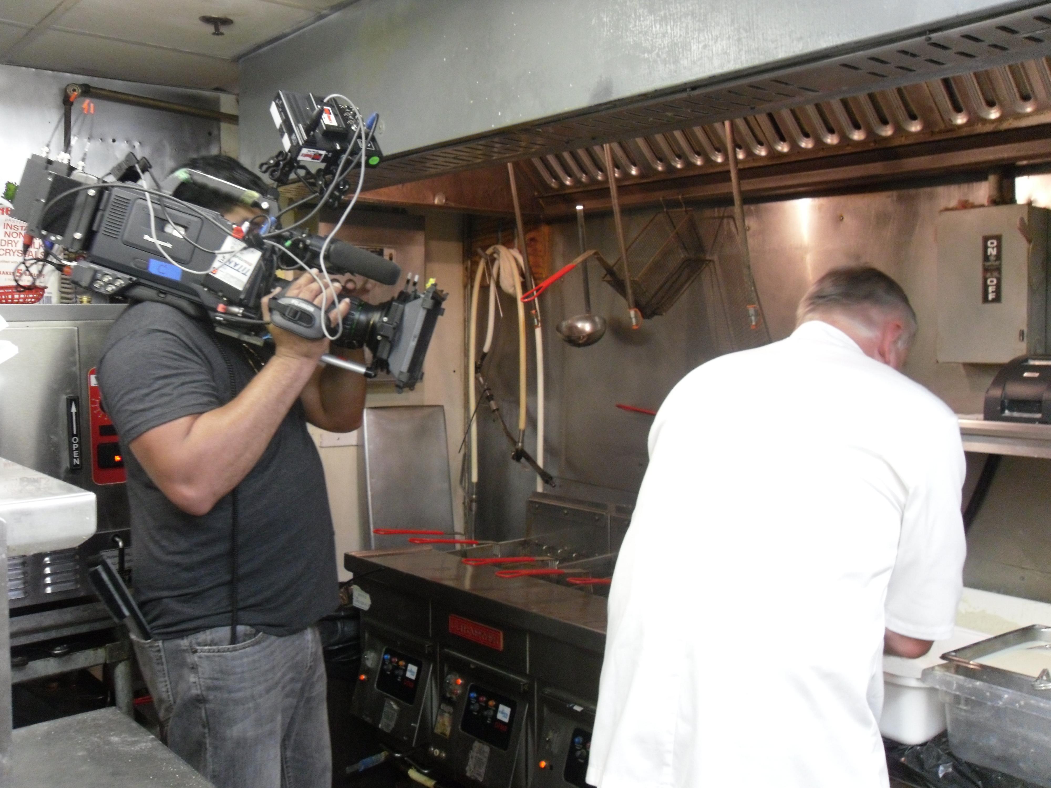 cameraman filming chef in kitchen