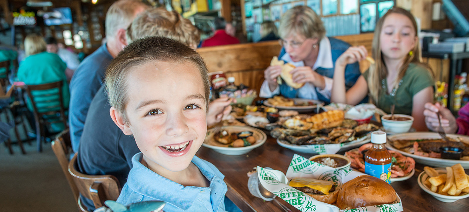 Family eating seafood at Original Oyster House Restaurant with boy smiling